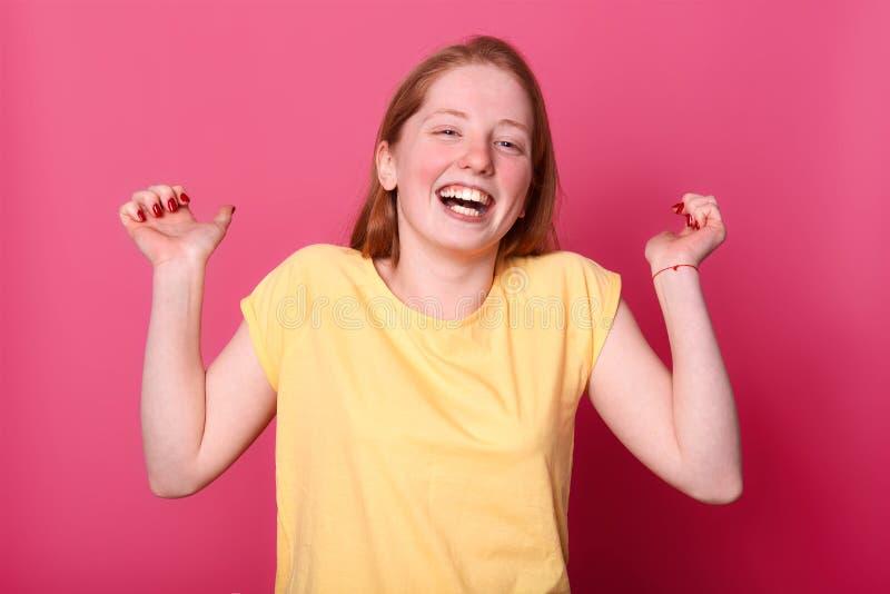 Studio strzelający szczęśliwa emocjonalna młoda kobieta w jaskrawy koloru żółtego t koszulowy śmiać się szczerze, utrzymuje ręki  obrazy stock