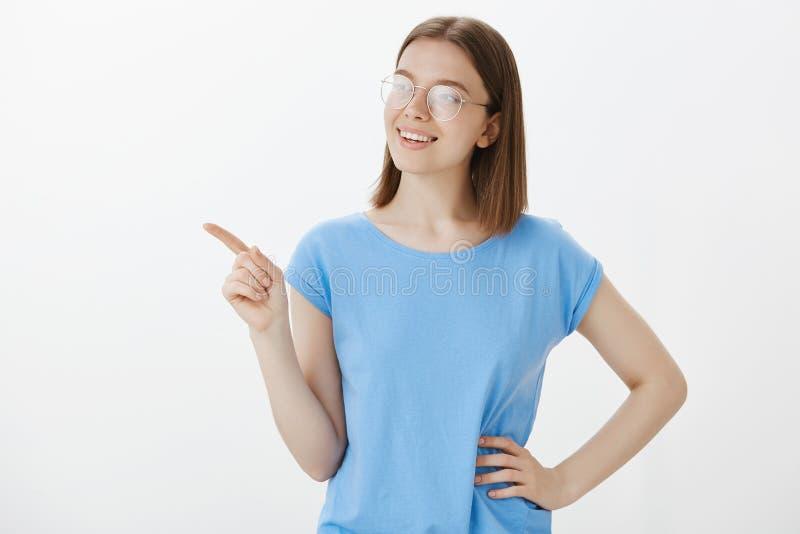 Studio tiré de l'étudiante européenne heureuse sûre dans l'équipement occasionnel, tenant la main sur la hanche, regardant fixeme photo stock