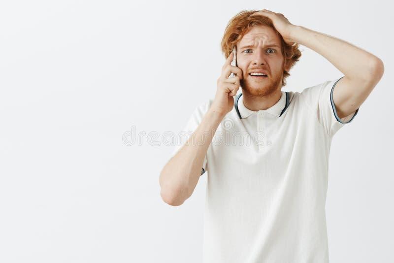 Studio tiré de l'homme roux inquiété commençant la panique tout en parlant au téléphone Portrait du type nerveux de désespoir fro photographie stock