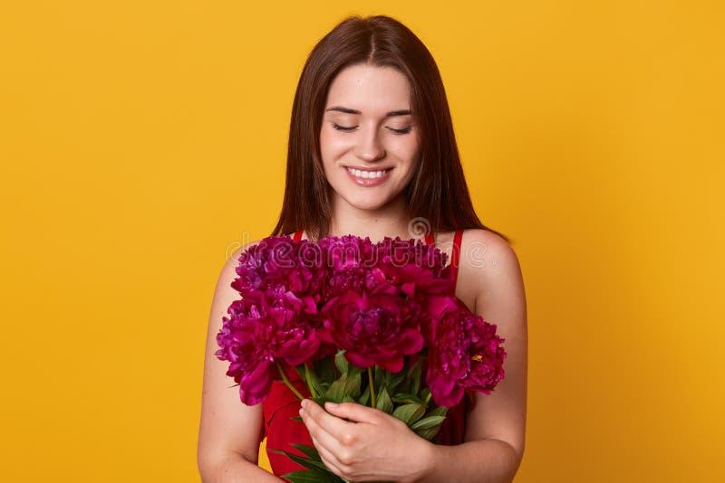 Studio tiré de la belle fille de brune tenant le grand bouquet avec des pivoines de Bourgogne Femme élégante heureuse avec des fl image stock