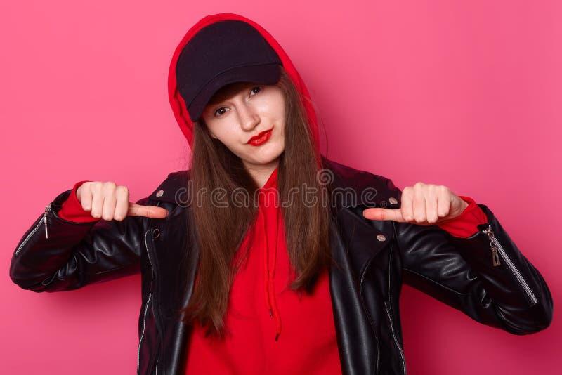 Studio tiré de la jeune fille fraîche effrontée habillée dans la veste hoody et en cuir rouge confortable, chapeau noir, points a photo libre de droits