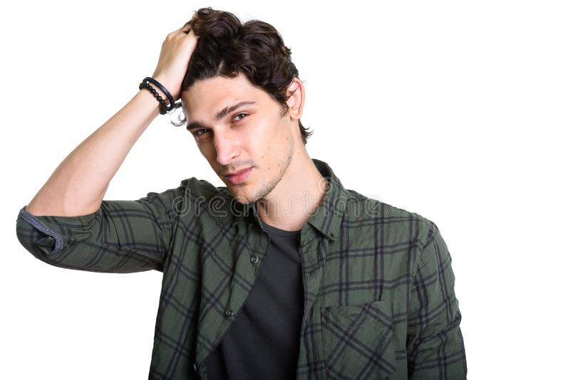 Studio tiré des cheveux de brossage de jeune homme bel de retour image libre de droits