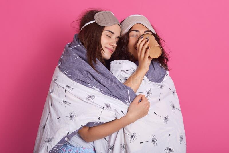 Studio tiré du café potable de femme tandis que son ami avec les eues fermés l'étreint pendant la partie de pyjamas, port d'amis  images libres de droits