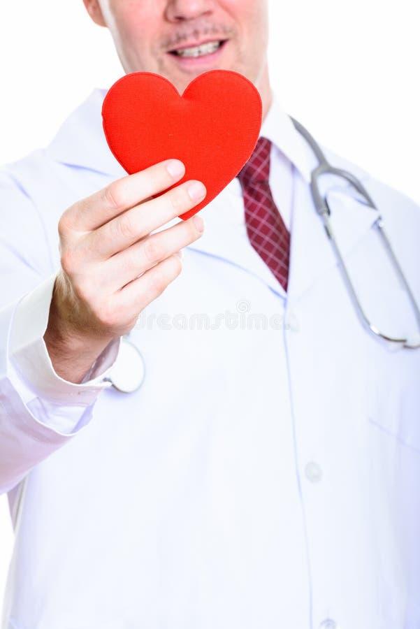 Studio tiré du docteur mûr heureux d'homme souriant tout en tenant le rouge photo libre de droits