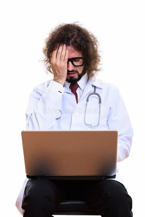 Studio tiré du docteur soumis à une contrainte d'homme utilisant l'ordinateur portable tout en couvrant f photographie stock