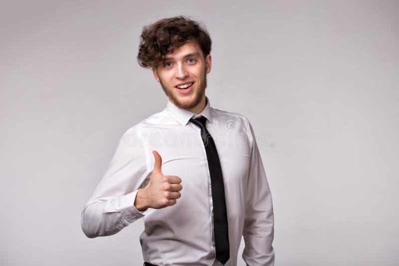 Studio tir? du jeune homme d'affaires attirant heureux et montrant des pouces, d'isolement sur le fond gris photographie stock