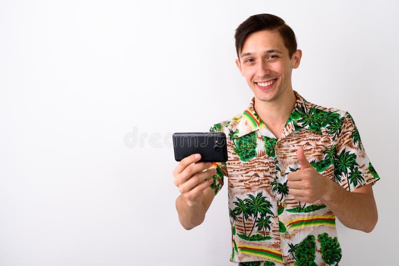 Studio tiré du jeune homme de touristes heureux souriant tout en donnant le thum photo stock