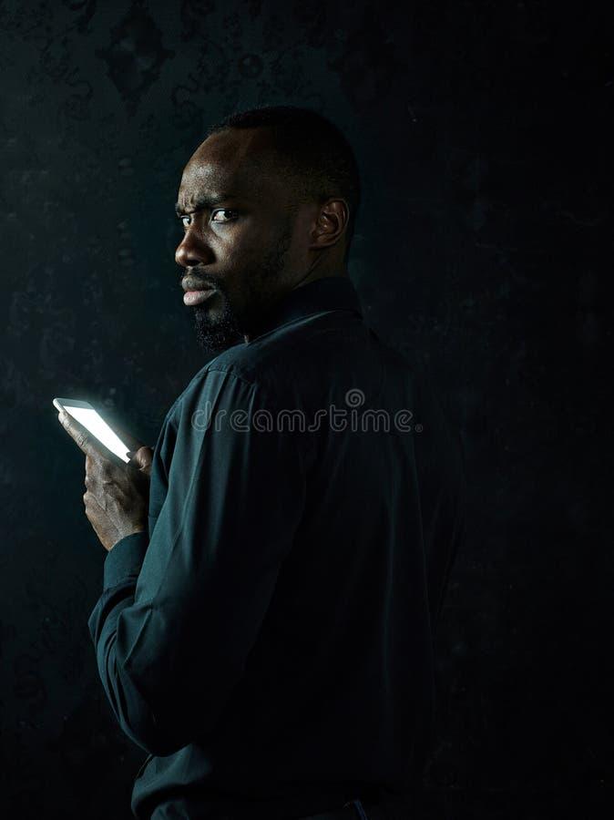 Studio tiré du jeune homme sérieux d'africain noir pensant tout en parlant au téléphone portable sur le fond noir image stock