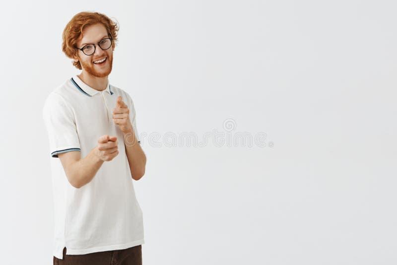 Studio tiré du jeune type roux caucasien drôle et mince avec la barbe en verres de connaisseur faisant des gestes d'amusement de  photographie stock