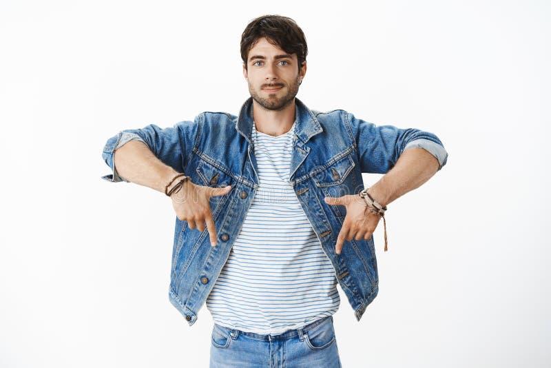 Studio tiré du mâle hispanique beau élégant avec la barbe et des yeux bleus dans la veste à la mode de denim au-dessus du T-shirt photos stock