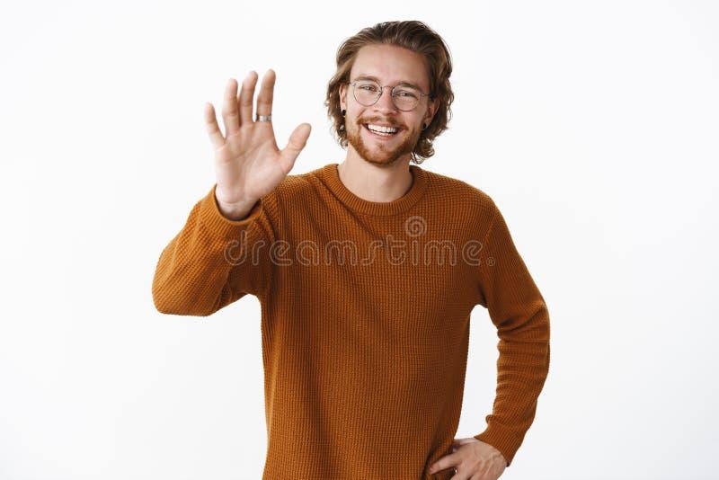 Studio tiré jeune de l'homme barbu amical et heureux ordinaire en chandail et verres ondulant la main augmentée dans bonjour le g image libre de droits