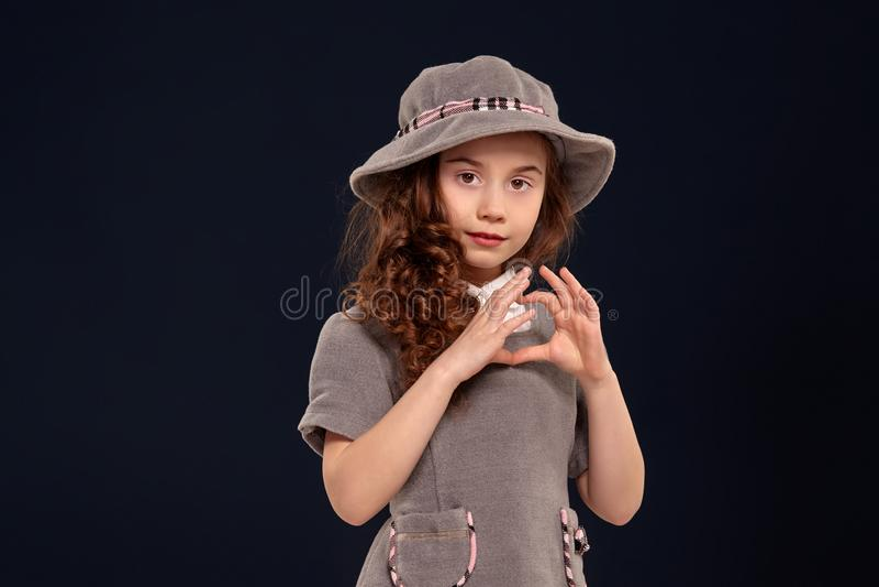 Studio tir? d'un beau petit enfant avec de longs, boucl?s cheveux posant sur un fond noir image stock