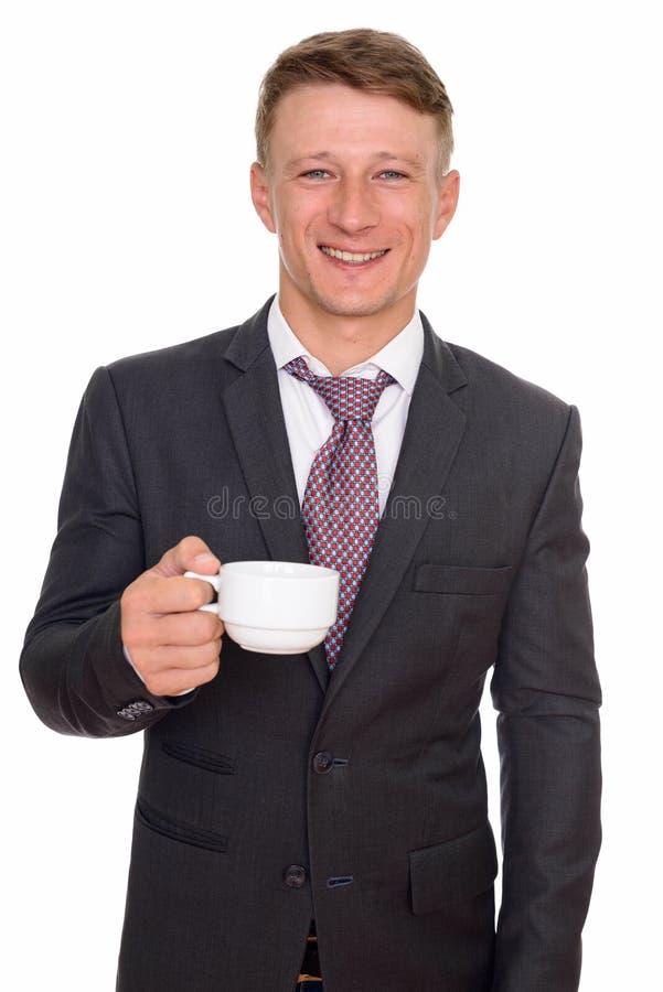 Studio van de jonge gelukkige Kaukasische koffie die van de zakenmanholding wordt geschoten royalty-vrije stock afbeeldingen