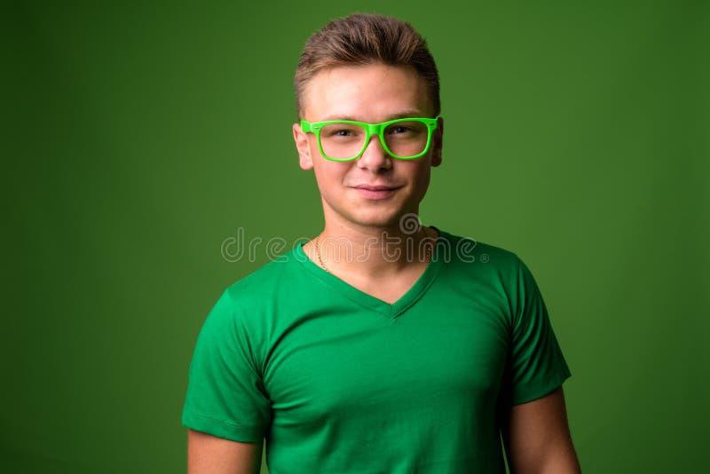 Studio van de jonge knappe mens tegen groene achtergrond wordt geschoten die stock foto's