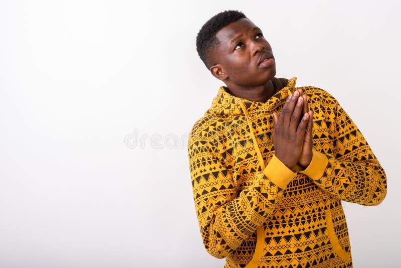 Studio van de jonge zwarte Afrikaanse mens wordt geschoten die terwijl het denken bidden die royalty-vrije stock foto