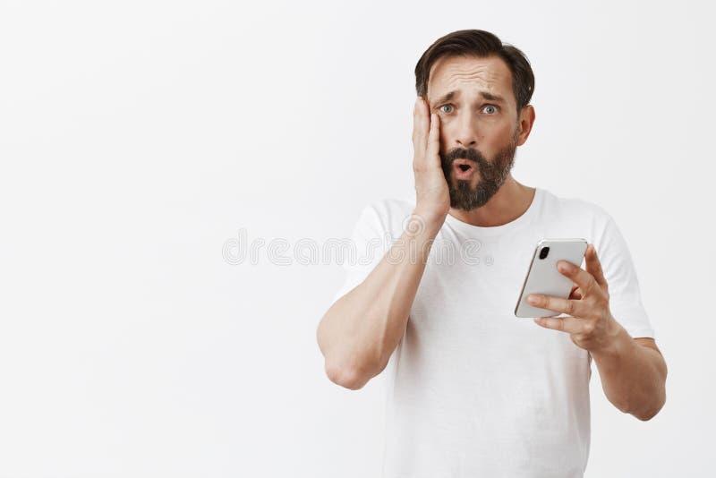 Studio van de ongelukkige ontstemde volwassen mens wordt die smartphone het scherm en het zien van rimpels, het vouwen van lippen royalty-vrije stock foto's