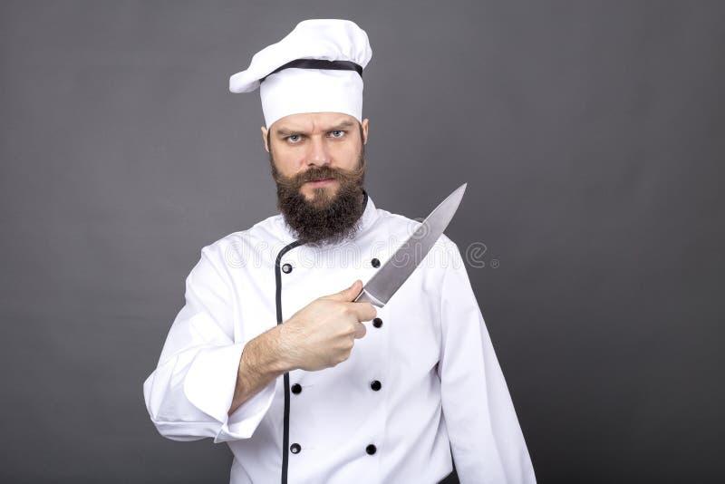Studio van een gebaarde chef-kok wordt geschoten die een groot scherp mes houden dat royalty-vrije stock foto's