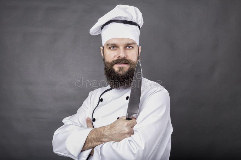 Studio van een gebaarde chef-kok wordt geschoten die een groot scherp mes houden dat royalty-vrije stock afbeeldingen