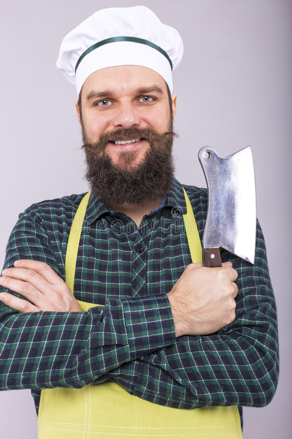 Studio van een gelukkige gebaarde mens wordt geschoten die een slagersmes houden dat royalty-vrije stock fotografie