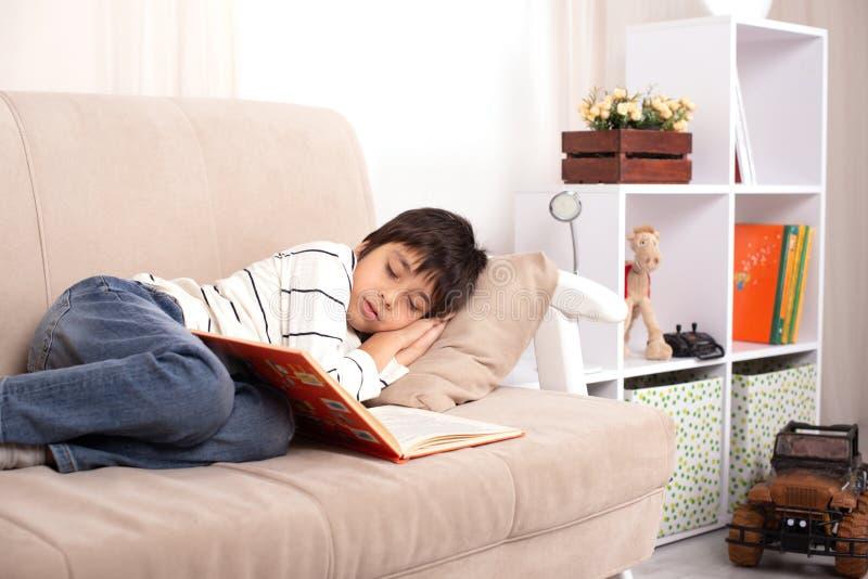 Studio van een jonge jongen wordt geschoten die een wit overhemd en jeans in slaap op de laag na het lezen van een boek in de rui royalty-vrije stock afbeeldingen