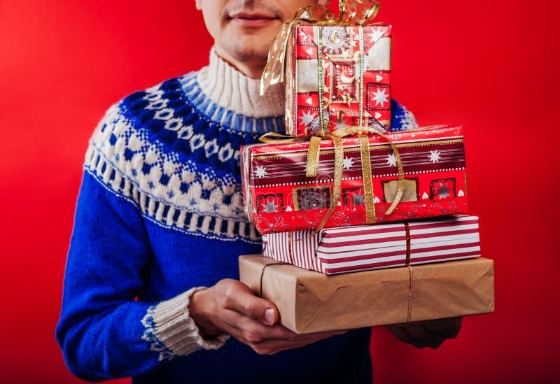 Studio van een jonge mens die in Ijslandse sweater wordt geschoten een hoop van giftdozen die houden Kerstmis of het Nieuwe conce stock foto's