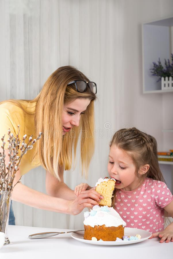 Studio van een jonge moeder wordt geschoten die haar dochter een Pasen voeden die cupcak stock foto's