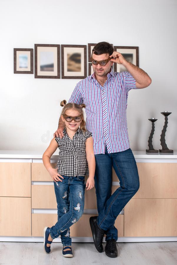 Studio van een klein meisje en haar papa wordt geschoten die zich in de ruimte in identieke punten dezelfde manier bevinden die D stock fotografie
