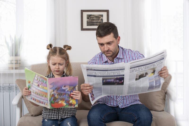 Studio van een klein meisje en haar papazitting op de bank en lezing de kranten samen zelfde manier wordt geschoten die De dochte stock fotografie