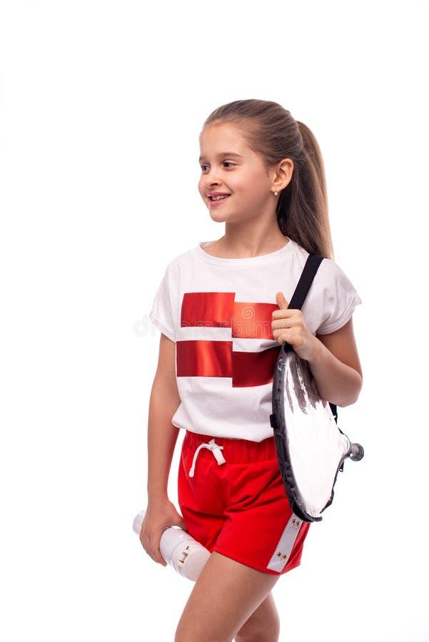 Studio van een weinig glimlachend meisje met een zak en een geïsoleerde die thermosfles van de tennisracket wordt geschoten, royalty-vrije stock foto