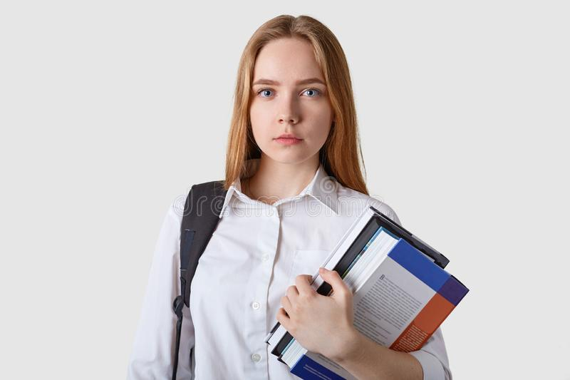 Studio van ernstige Kaukasische eerlijke haired jonge vrouw met document omslag in handen, die witte blouse dragen, die camera be royalty-vrije stock afbeelding