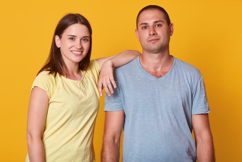 Studio van gelukkig positief jong paar wordt geschoten die en bij camera, meisje bekijken glimlachen die gele t-shirt dragen die  stock fotografie