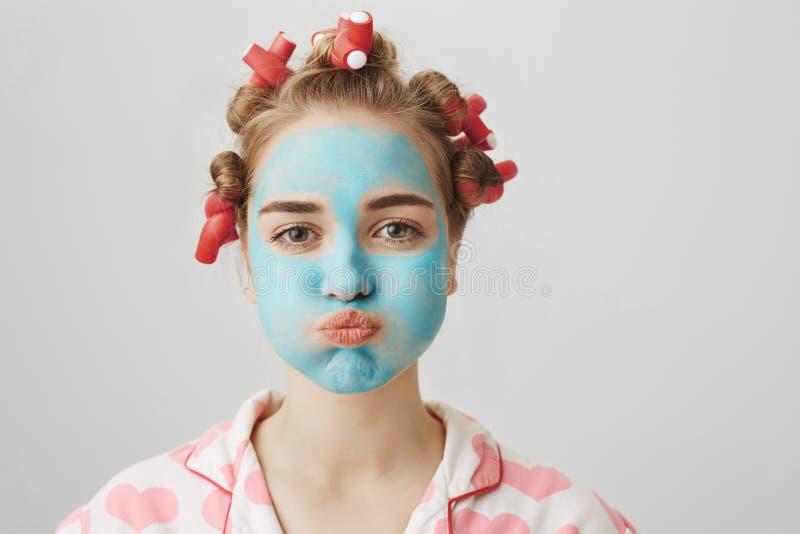 Studio van grappige huisvrouw in haar-krulspelden en nachthemden, mokken terwijl status met gezichtsmasker en het doen wordt gesc stock fotografie