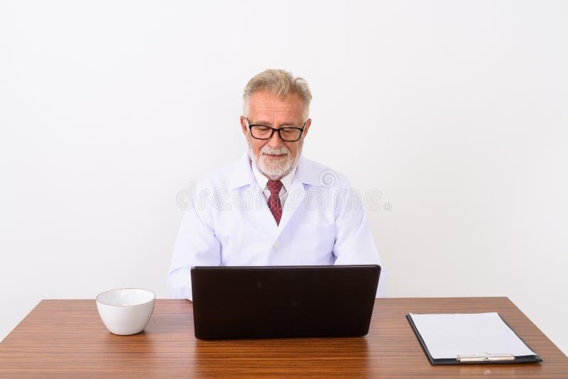 Studio van het gelukkige hogere gebaarde mens arts glimlachen wordt geschoten terwijl usi die stock afbeeldingen