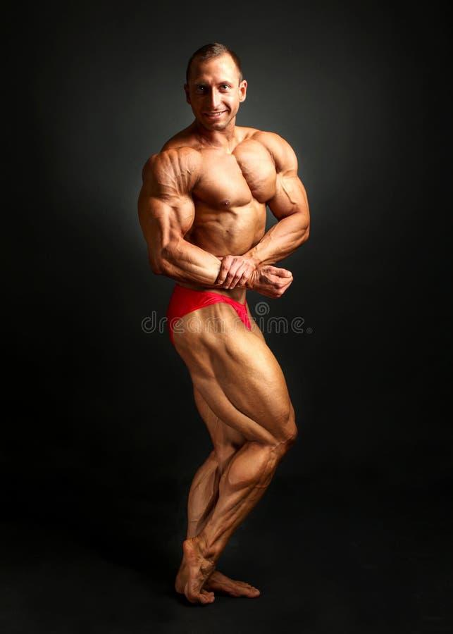 Studio van het mannelijke bodybuilder stellen, verbuiging en het tonen wordt geschoten bice die stock afbeeldingen