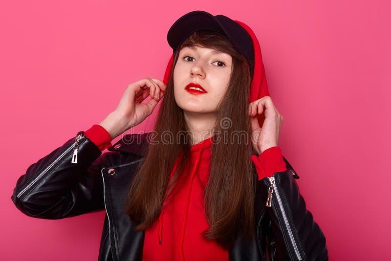 Studio van jong mooi tienermeisje wordt geschoten die rood hoody en leerjasje dragen, direct bekijkend camera die met prettige ge royalty-vrije stock afbeeldingen
