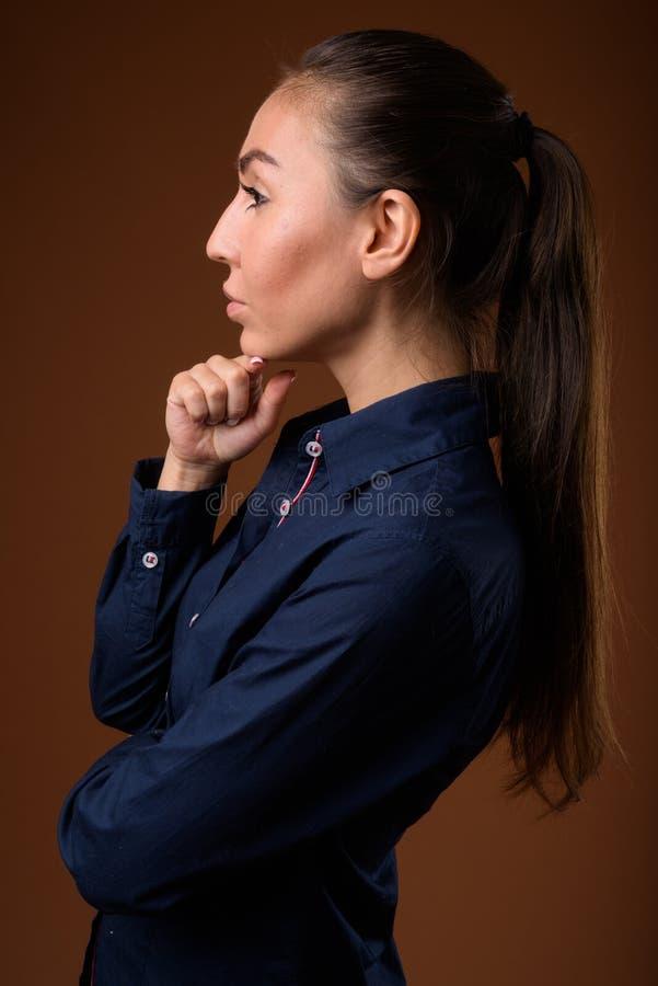 Studio van jonge mooie onderneemster tegen bruine backg wordt geschoten die stock foto