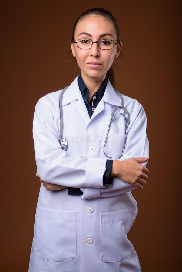 Studio van jonge mooie vrouw arts tegen bruine backgr wordt geschoten die stock foto
