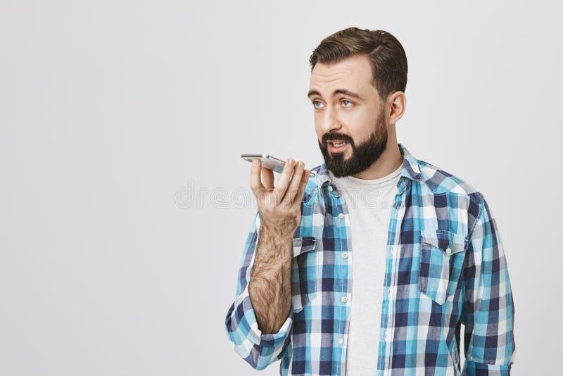 Studio van mannelijke Europese volwassen holdingstelefoon dichtbij mond wordt terwijl het spreken aan het op spreker, die zich te royalty-vrije stock foto's