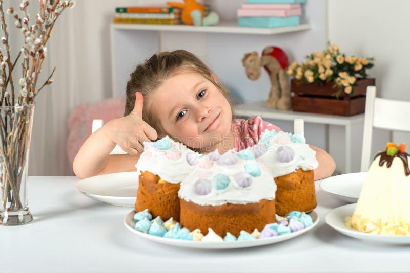 Studio van meisjezitting bij een lijst met Pasen-cakes wordt geschoten die Zij toont duim op gebaar dat Pasen-de cake zeer smakel royalty-vrije stock foto