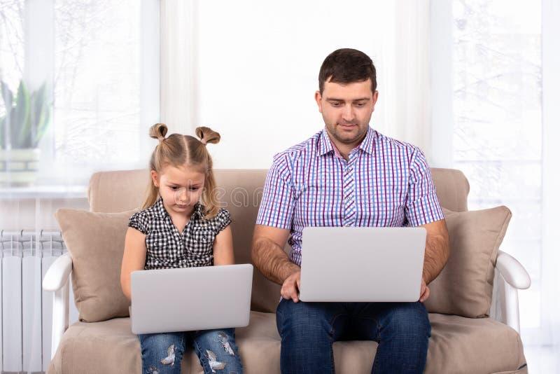 Studio van meisjezitting wordt geschoten met papa op bank die thuis met laptops De dochter imiteert papa royalty-vrije stock fotografie
