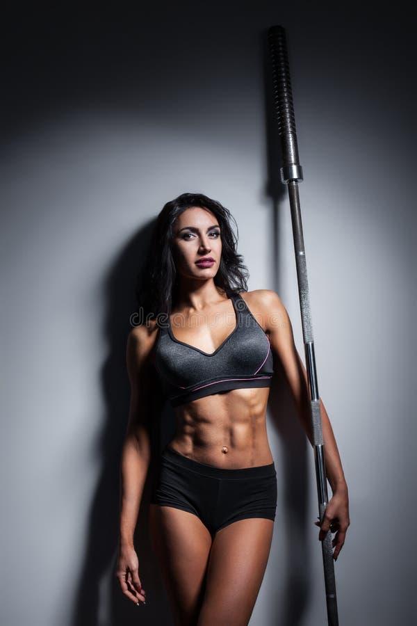 Studio van perfect lichaam van bodybuilderwijfje wordt geschoten met barbell die; royalty-vrije stock afbeelding