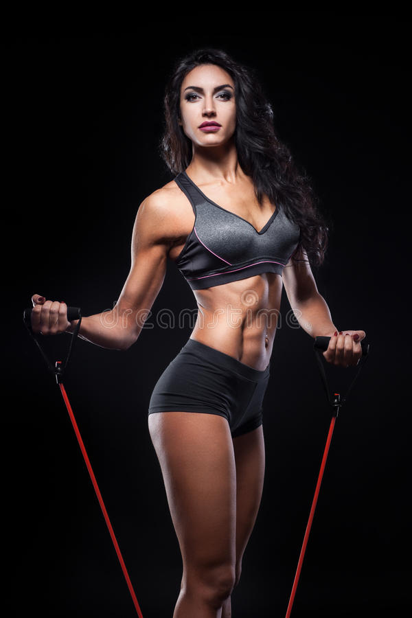 Studio van perfect lichaam van bodybuilderwijfje wordt geschoten met expander die; royalty-vrije stock foto