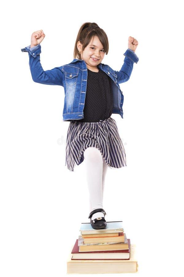 Studio van succesvol meisje met één been op een stapel van boeken wordt geschoten dat stock foto
