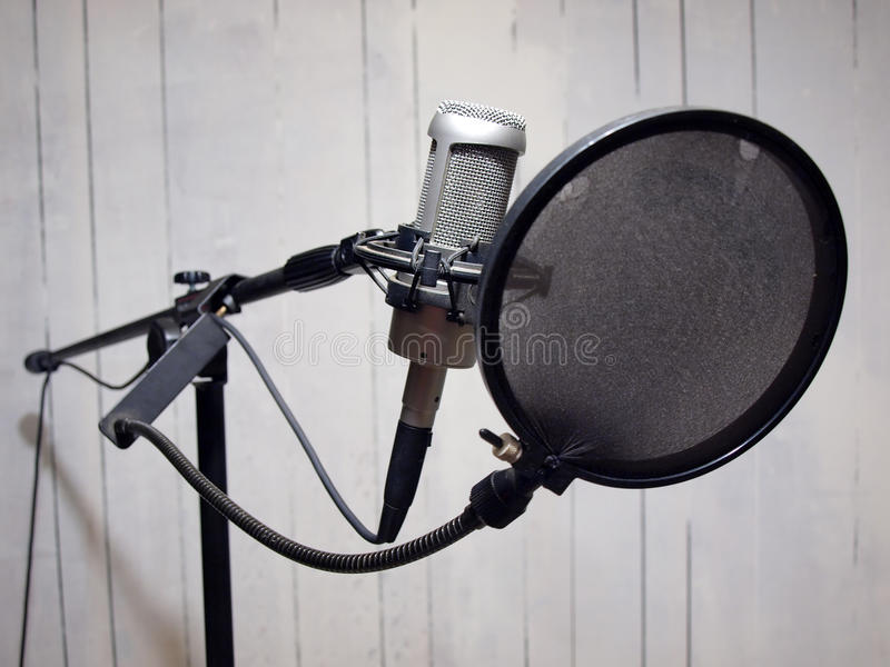 Studio vocal microphone & grunge wall 2. A studio vocal microphone with a grunge styled wall in the background. This photo includes copy and cropping space royalty free stock image