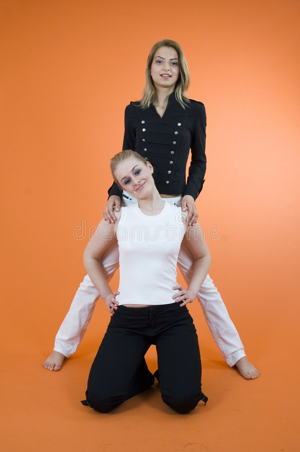 Studio Women 1. Two blond women, one standing behind the second woman kneeling. In studio with orange background stock photo