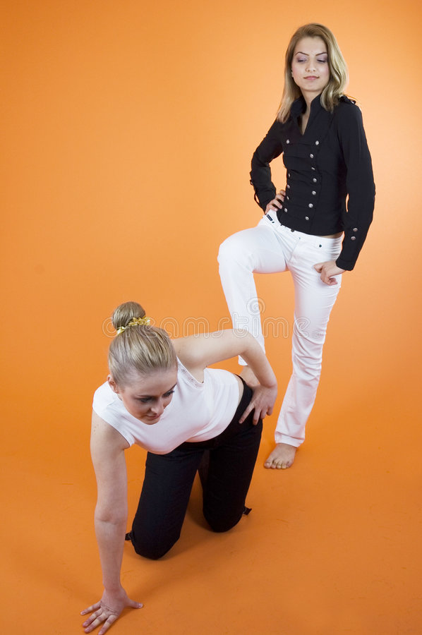 Studio Women 2. Two blond women, one kneeling and bending over while the second has one foot on the first woman's back. In studio with orange background royalty free stock photos