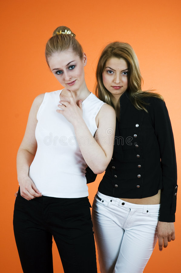 Studio Women 3. Portrait of two blond women standing close together side by side. In a studio setting with orange background stock image