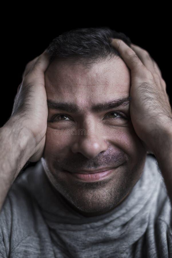 Studioabschluß herauf Porträt eines verrückten Mannes, der oben mit den Händen auf seinem Kopf schaut stockfoto