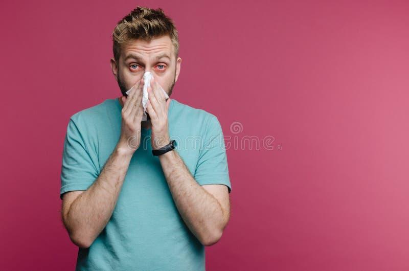 Studiobeeld van een jonge mens met zakdoek De zieke ge?soleerde kerel heeft lopende neus de mens maakt een behandeling voor de ve stock foto