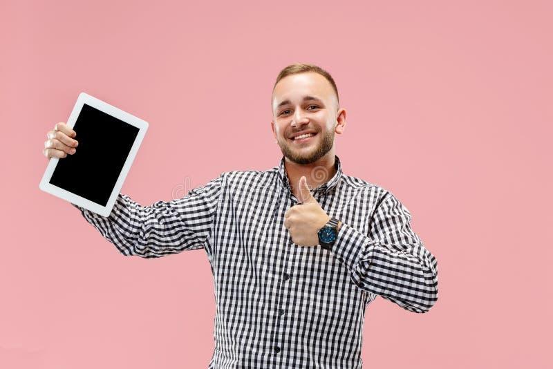 Studiobild av den positiva mannen som isoleras på rosa bakgrundsanseende i tillfällig kläder som rymmer minnestavlan och visar de royaltyfri bild